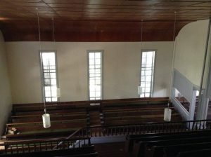 photo of a white wall with large windows and a brown curved section where the wall reaches the ceiling. rows of benches are below.